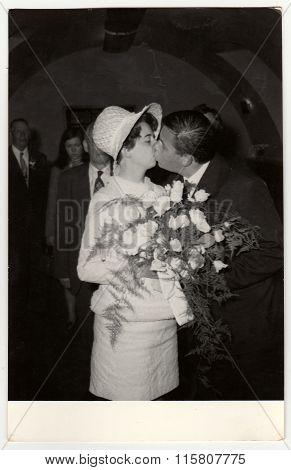 A vintage photo shows wedding photo - bridal kiss, circa 1970.