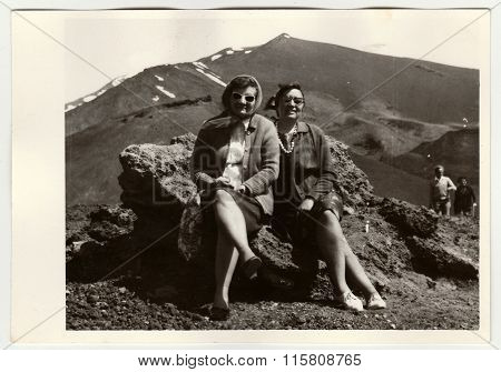 Vintage photo shows people on vacation, circa 1960s.