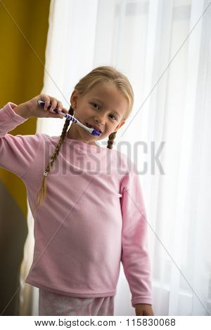 Dental hygiene. Happy little girl brushing her teeth near window