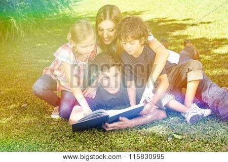 Happy family reading a book in garden in summer