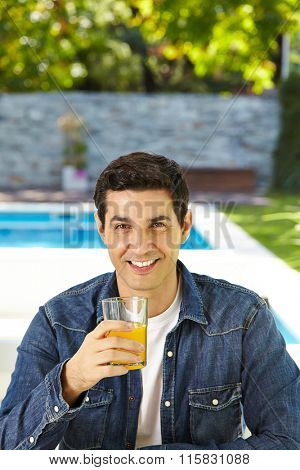 Happy man drinking fresh orange juice in summer