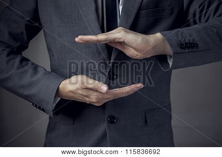 Businessman In Suit With Two Hands In Position To Protect Something (focus On Hand, Blur Out The Sui