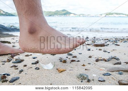 Man barefoot walking on the beach, with risk to step on piece of glass, concept of dangerous waste o