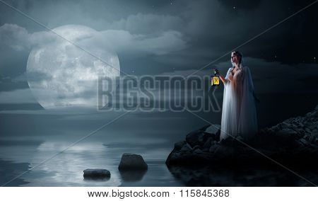 Young elven girl with lantern on night sea coast