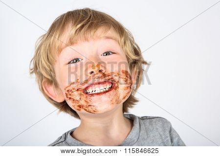 Young messy boy with chocolate on his face
