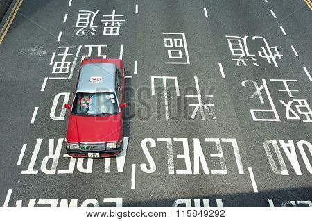 Red Taxi Driving In The Central District Of Hong Kong Island