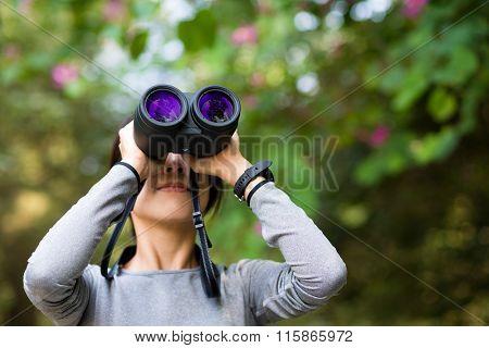 Woman looking though binocular in jungle
