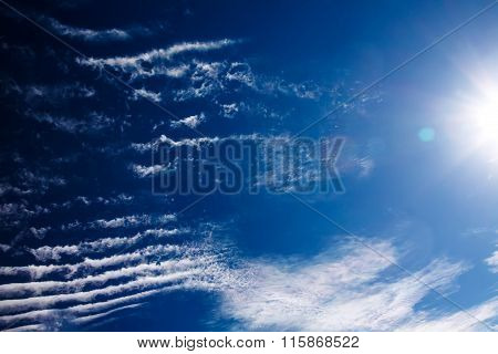 White spindrift clouds on blue sky with sun