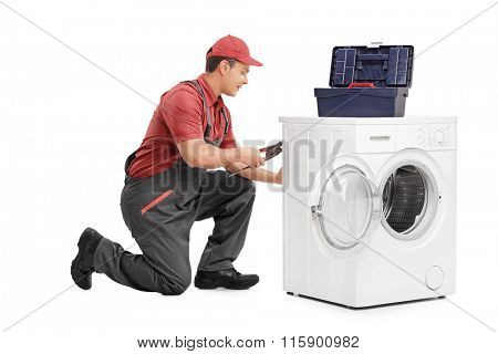 Studio shot of a young male worker repairing a washing machine isolated on white background
