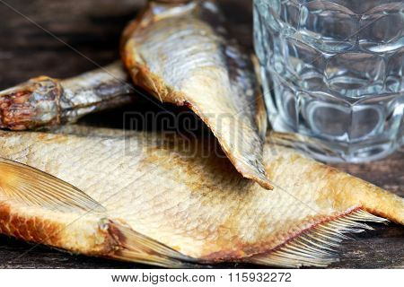 Beer and Salted Dry fish vobla on wooden table