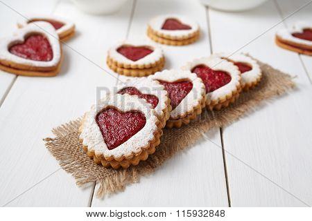 Heart shaped cookies with jam, delicious homemade holiday surprise sweet on white wooden background