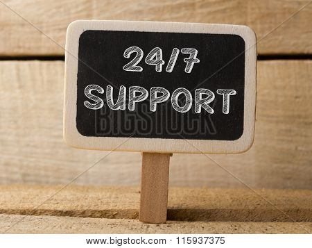 Support 247  text write on Chalkboard at wooden background