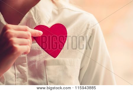 Heart shape love symbol in woman hands with white shirt pocket Valentines Day