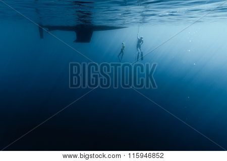Two free divers training in the open sea along the anchor chain of the vessel
