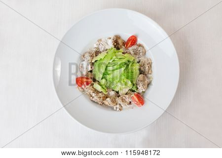salad with meat in a creamy sauce, ase, lettuce, romaine, iceberg cherry tomatoes on top of the plat