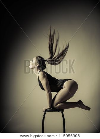 Bodybuilding. Atletic woman fit slim body posing with hair blowing on dark background. Sepia aged tone poster