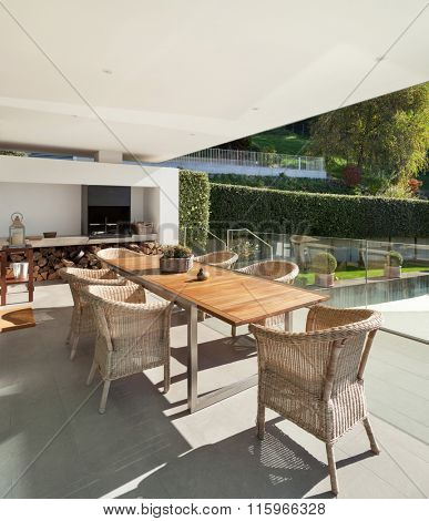 beautiful veranda with wooden table and wicker chairs, exterior