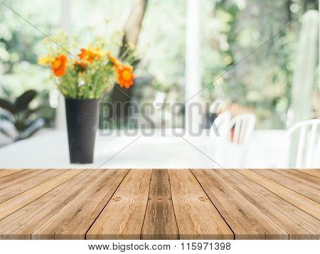 Wooden Board Empty Table blur flower vase in coffee shop - can be used for display or montage.
