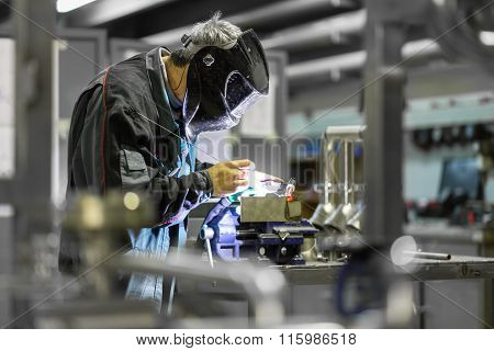 Industrial worker welding in metal factory.