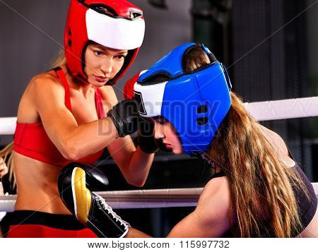 Two agressive women boxer wearing helmet boxing at ring .