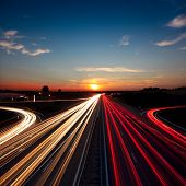 Speed Traffic light trails on motorway highway at sundown, long exposure, urban background with sun and dark sky poster