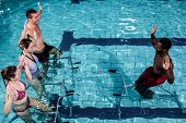 Fitness class doing aqua aerobics on exercise bikes in swimming pool poster