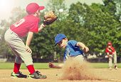 Boy sliding into base during a baseball game with Instagram style filter poster