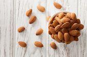 almond nut organic healthy snack vegan vegetarian white background wood teak rustic still life poster