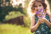 Happy child girl playing with bouquet of bluebells in summer. Happy childhood outdoor activities. Exploring nature and picking flowers. Cozy country vacations. poster