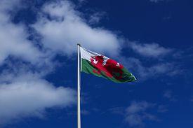 Welsh flag flies against blue sky
