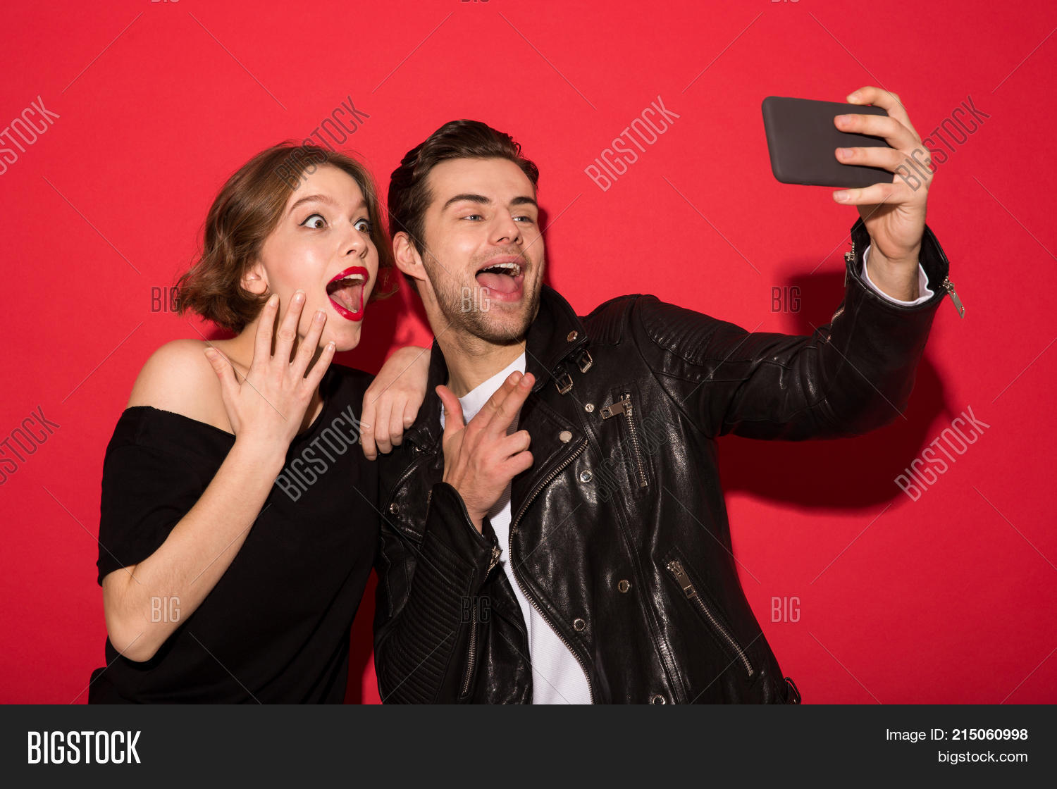 Image Of Happy Screaming Punk Couple Posing And Making Selfie On Smartphone Over Red Background