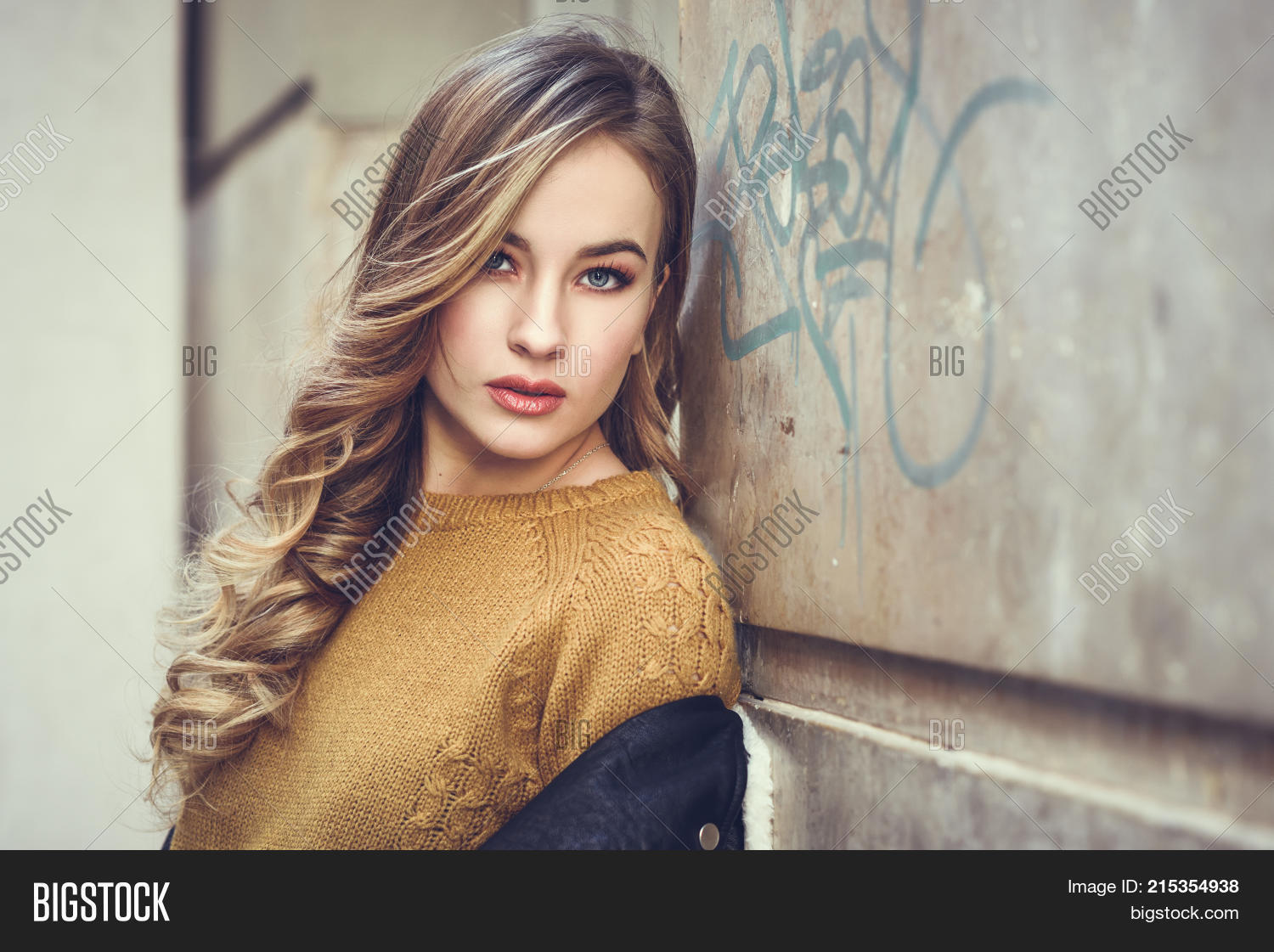 055268ee1 Blonde woman in urban background. Beautiful young girl wearing black  leather jacket and mini skirt standing in the street. Pretty russian female  with long ...
