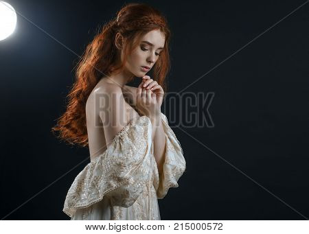 Portrait of a young red-haired woman in a vintage ash dress with open back and shoulders in the moonlight on a black background. A princess. Fairy tale. Art photo