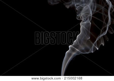 Smoke volutes on a pure black background