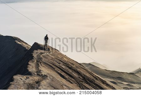 A lone man gazes at a sea of clouds on top of a mountain crest at sunrise.