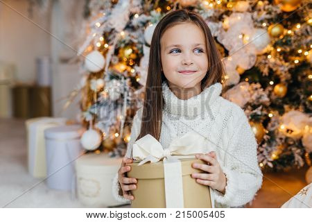 Cute lovely small kid with charming appearance, glad to recieve Christmas gift, looks aside with happy expression, has intrgue what present is, poses near beautiful decorated fir tree.