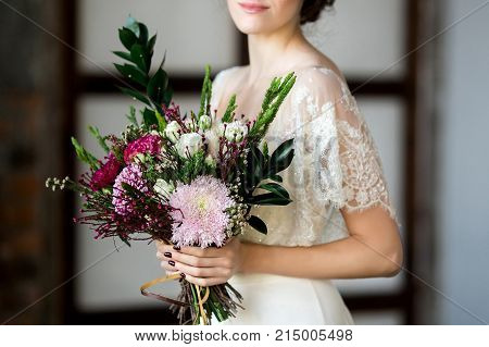 Beautiful Bride holding big wedding bouquet on wedding ceremony