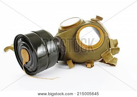 Gas mask from real war. Used vintage green and black gas mask can illustrate danger, war, catastrophe, or other concept. Gas mask on isolated white studio background. Easy to use for your work. Green old gas mask.