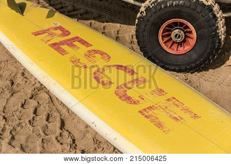 Yellow surfboard on the sand with the word rescue in red