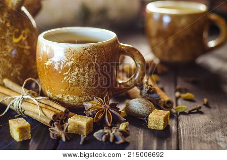 Tasty hot coffee with grains and spices on table