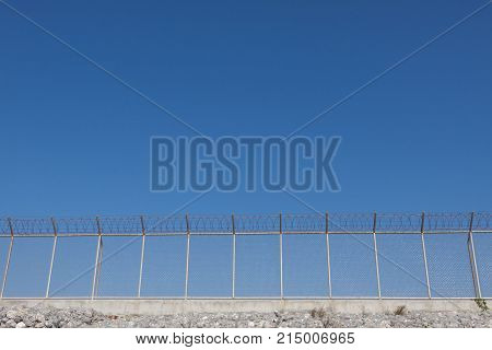 Security with a barbed wire fence and blue sky.