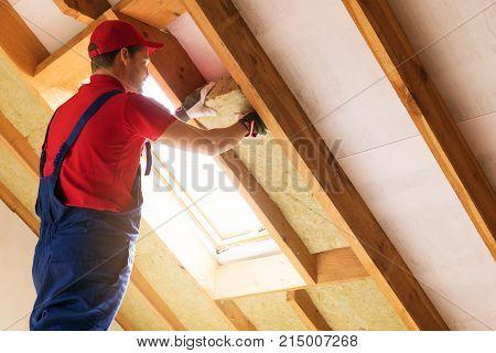 house attic insulation - construction worker installing rock wool in mansard wall