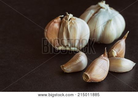 Garlic put on black granite table in side view with copy space isolated background. Food preparation concept for garlic in still life idea. Fresh garlic ready to use. Famous spices or herbs for Asian food is garlic.