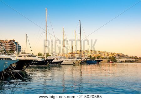 Sailing and luxury motor yachts in marina of Zeas. Sunset and view of Kastela in the background. Piraeus city Greece.