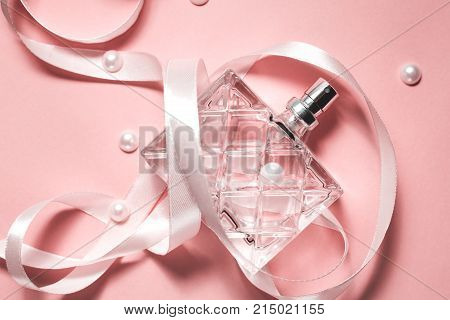 Bottle of modern perfume on pink background