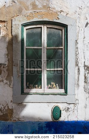 Closed old dusty window with a green inner shutter and little toys in the window. Old weathered facade. Bright blue base of the house. Faro Portugal.