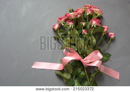 Bouquet of pink spotted bush roses with pink ribbon on gray background. Top view. Romantic or Valentine's card with love.