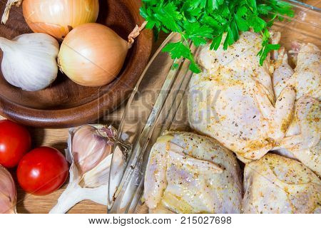 Cooking meat quails in the oven. Whole quail marinovani in spices with onions and mustard. Garnish with fresh potatoes and parsley.