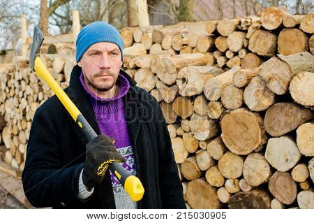 A man is a woodcutter with an ax against the background of a pile of firewood.