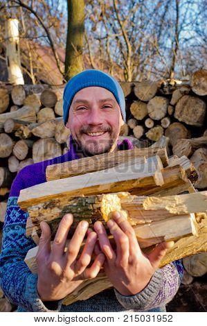 The woodcutter holds firewood in hand. Portrait of woodcutter.